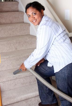 uso domestico: Donna delle pulizie nella sua casa con un aspirapolvere