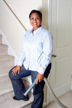 ama de llaves: La mujer de limpieza en su casa con una aspiradora