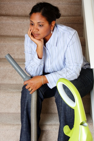 black appliances: Woman cleaning in her house with a vacuum cleaner