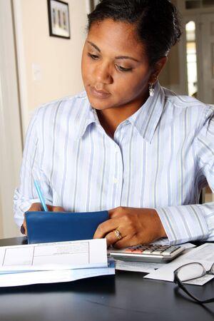 checkbook: Mujer sentada en una mesa el pago de facturas