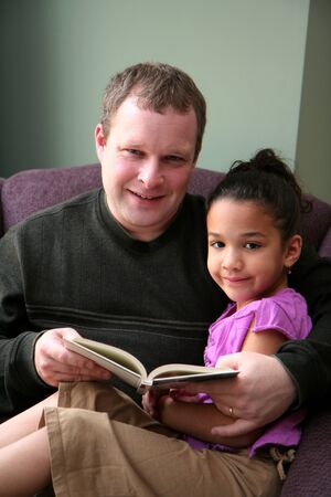 Father reads a book to his young daughter photo