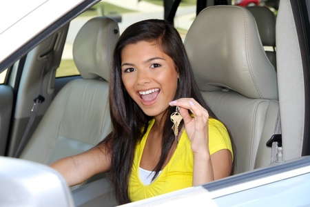 Teen holding up keys to her new car Archivio Fotografico