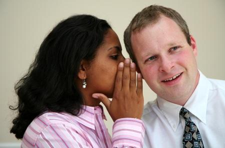 Woman telling a man a secret Banco de Imagens