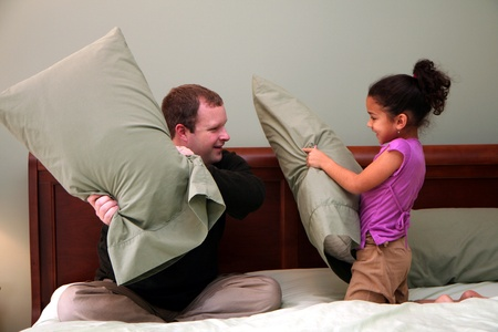 Father and Daughter having a pillow fight photo