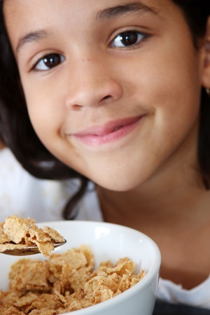 Girl eating her breakfast sitting at the table photo