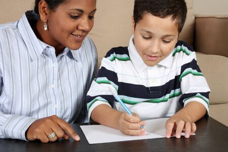 Interracial family sitting together writing on paper photo
