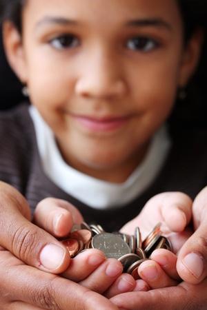 お子様の手に座っているコインの山
