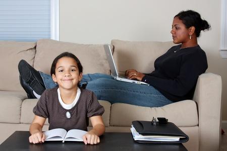 werkende moeder: Minority vrouw en haar dochter in de woonkamer
