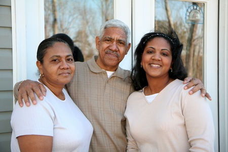 american house: Minority family standing outside their new home