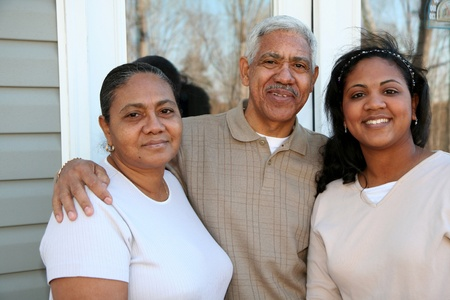 Minority family standing outside their new home Stock Photo - 13298040