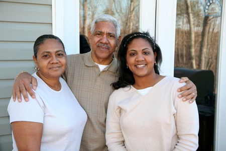 Minority family standing outside their new home Stock Photo - 13298043