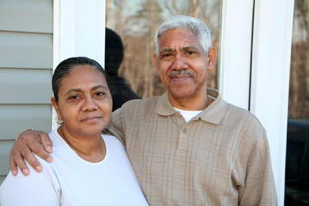 Minority couple standing in front of their home photo