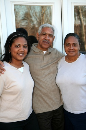 Minority family standing outside their new home photo