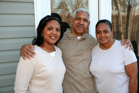 Minority family standing outside their new home Stock Photo - 13298249