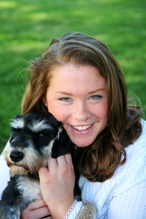 Caucasian teenage girl with brown hair with her dog photo