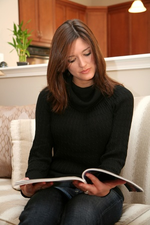 A young woman reads a magazine while sitting on her couch Stock Photo - 13317368