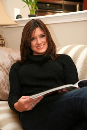 A young woman reads a magazine while sitting on her couch Stock Photo - 13316963