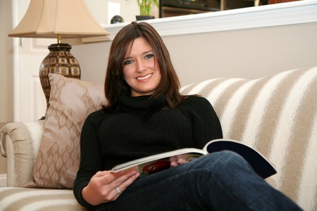 A young woman reads a magazine while sitting on her couch Stock Photo - 13317644