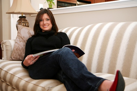 A young woman reads a magazine while sitting on her couch Stock Photo - 13317850