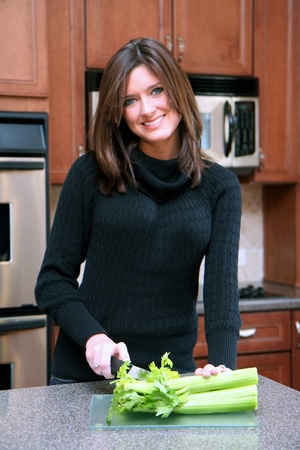 woman knife: Woman with blue eyes standing in her kitchen