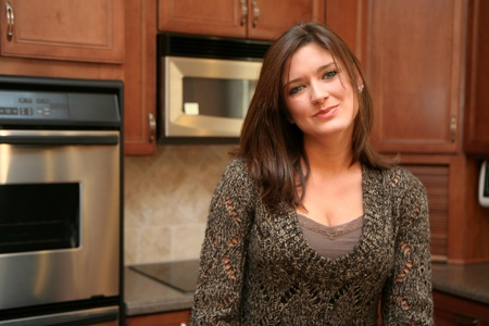 Woman with blue eyes standing in her kitchen