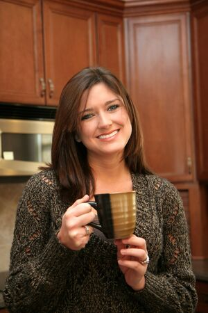 A young woman in her kitchen drinking coffee Stock Photo - 13317723