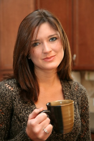 A young woman in her kitchen drinking coffee photo
