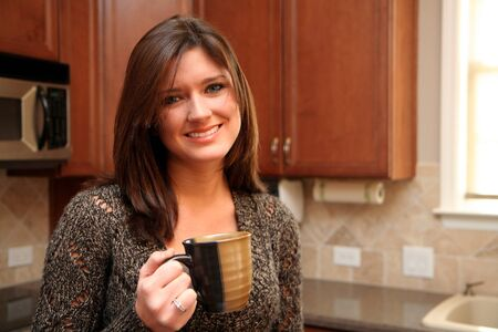 A young woman in her kitchen drinking coffee Stock Photo - 13317342
