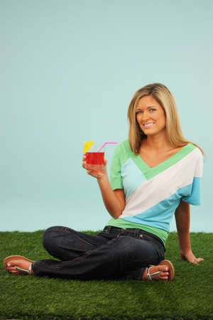 Woman Sitting Outside In The Grass With A Drink Stock Photo - 13317880