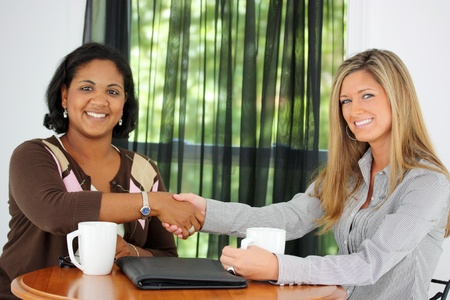 Two Women Shaking Hands In An Office 版權商用圖片