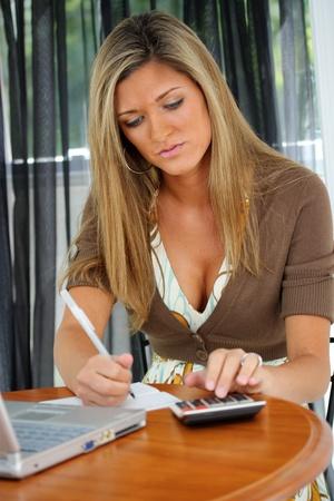 checkbook: Mujer joven feliz trabajando en la computadora