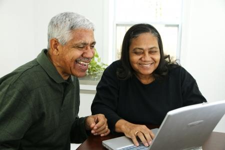 senior ordinateur: Famille ensemble � l'int�rieur de leur maison Banque d'images