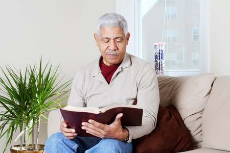 bible reading: Man reading the bible in his home Stock Photo
