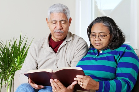 study: Couple reading the bible in their home