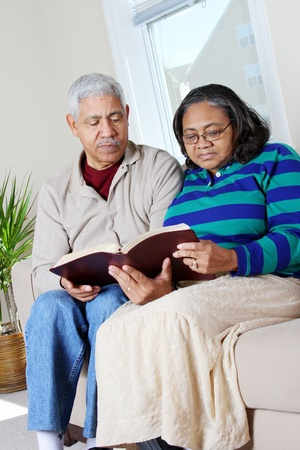 Couple reading the bible in their home photo