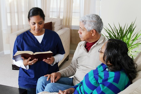 Couple reading the bible in their home with caregiver