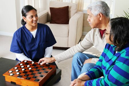 Home health care worker and an elderly couple playing game Stock Photo - 13398855