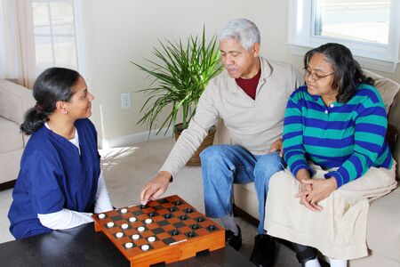 care at home: Home health care worker and an elderly couple playing game Stock Photo