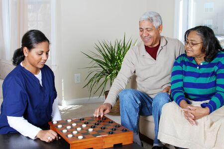 Home health care worker and an elderly couple playing game photo