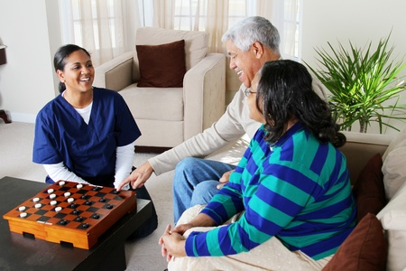 home health care: Home health care worker and an elderly couple playing game Stock Photo