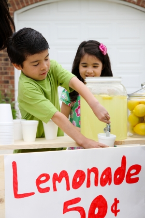 Children selling lemonade in front of their home photo