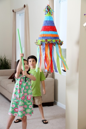 Kids hitting a pinata at birthday party photo