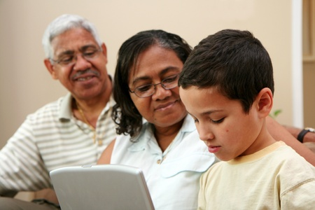 Child on computer with his grandparents photo