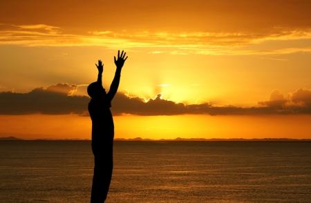 hombre orando: Hombre con las manos en alto mirando la puesta de sol