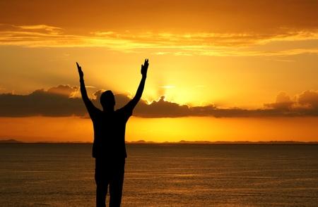 De mens met zijn handen omhoog kijken naar de zonsondergang