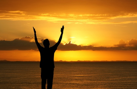 Man with his hands up watching the sun set Stock Photo - 13408558