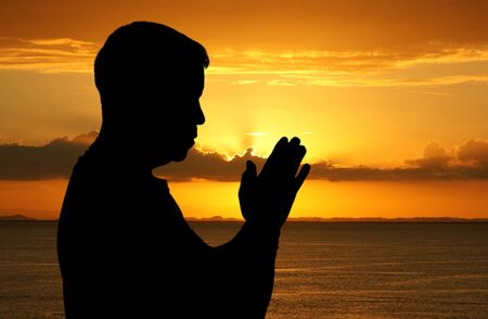 strong: Man praying with his hands folded at sunset