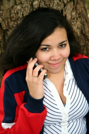 Teenager with a cell phone talking outside Stock Photo - 13410248