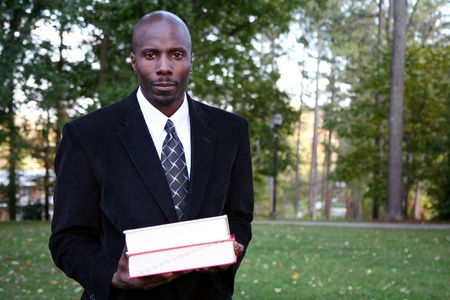 Teacher stands with books before class at college photo