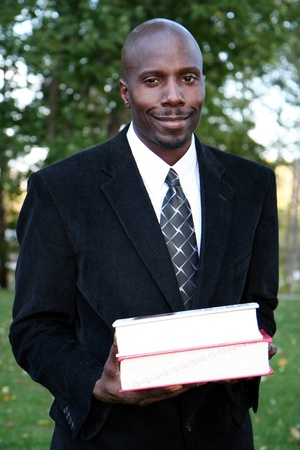 Teacher stands with books before class at college Stock Photo
